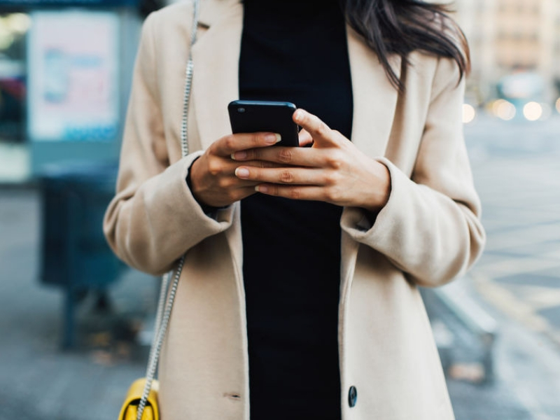 Stylish woman in the city using smartphone